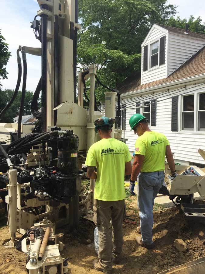 Nick Kolenda (left) and Tom Hartwell, Drillers for Active Environmental Technologies, use a 3230DT to install 2-inch monitoring wells in a residential area.  Monitoring wells were installed to determine potential groundwater impact.