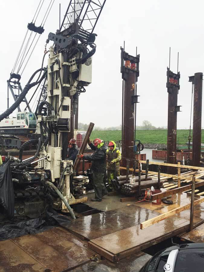 (l to r) Randy Crandell (at the controls), Shaun Biggs, and Chris Ruschmeyer add a stick of 6-in. casing to be advanced over a 4-in. core barrel using the 8140LC rotary sonic on a barge.